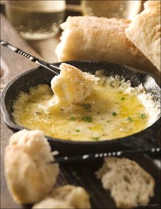 cast-iron-skillet-fondue  2 tablespoons extra-virgin olive oil  1 large garlic clove, finely minced  1-1/2 pounds Italian fontina, rind removed and small-diced  ½ teaspoon dried thyme leaves  kosher salt and freshly ground black pepper  crusty French baguette, for dipping