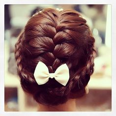sweet braided updo for short hair! Looks like the stylist divided the hair into three sections, french braided the middle, made a lace braid on both sides, tucked all the ends inside and hid it with a bow clip.