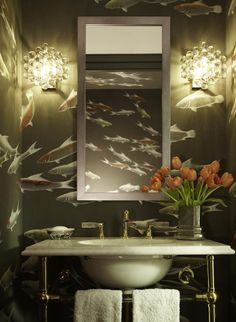 The walls of this California powder room are covered with hand-painted de Gournay wallpaper. The bubbly, Italian glass antique sconces and the frosted glass tap handles extend the watery theme of the fish wallpaper. Design by Katie Ridder; photo by Eric Paisecki