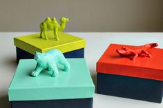 Plastic animals from the dollar store spray painted to create animal favor box toppers