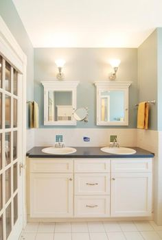 Dual sinks in the master bathroom are simple in design and complemented by matching era-appropriate medicine cabinets and lighting.