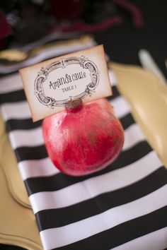 black, white and red: pomegranate place card with striped napkin