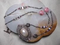 "This pretty 24"" necklace begins with the pendant, an oval copper plated filligree design with a large oval pale pink pearl & four light pink rhinestones. I created the necklace with copper chain and sections of beads in matching shades of pinks an..."