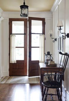 Beautiful Entryway/Foyer, wood and white, love the cafe curtains on the front doors...