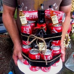 """Forget beer """"cakes""""! Made my husband this Jack and Coke cake for Fire Academy Graduation out of a large bottle of Jack, several cans of coke, smaller bottles of Jack with honey (the candles) and then some black duct tape and twine. Perfect country boy gift! Could possibly make a gin and tonic cake too, no?"""