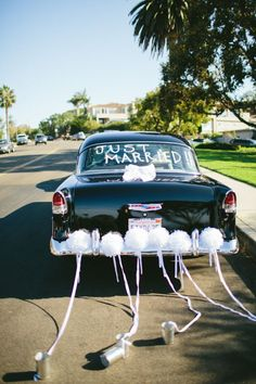 "Vintage ""Just Married"" getaway car with pom poms and tin cans"