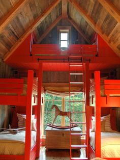 Sleeping loft built into a cathedral ceiling. The painted wood surfaces contrast with the natural treatment of the beams and paneling.