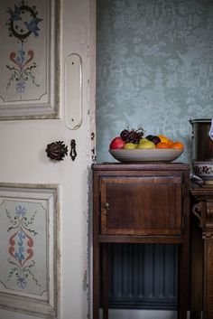 muted colour paintwork and wallpaper with accent pop colour in the fruit bowl - work of art feel