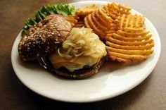 """The Graystone boasts Swiss, mozzarella and cheddar cheese on a half-pound Angus beef patty, topped with fried white onions. """"It's Wisconsin,"""" said Graystone Ale House co-owner Jess Miller. """"It's got the three cheeses, a little more of a gourmet-style burger than what people might be used to from The Bar."""" / Evan Siegle/Press-Gazette photo"""