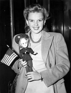 Judy Garland arrives in Penn Station, New York City, on a tour singing at U.S.O. camps. Here she holds a U.S. marine doll, 7/2/43.