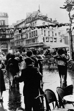 Couples dancing in the streets of Paris in the rain to celebrate July 14th, France's national holiday. 1954.