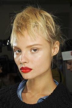 Red lips, natural face and undone french twist with the ends brought on top of the head to give the illusion of roughly cut fringe at Prada Spring 2013