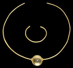 A THRACIAN GOLD TORQUE AND BRACELET   CIRCA 5TH CENTURY B.C.   Both fashioned from a stout wire, round in section, forming an open ellipse, the flat terminals with incised geometric ornament, a gold and rock crystal pendant threaded onto the torque, perhaps a modern addition, the sides of the pendant with two rows of beaded wire framing a band of hollow hemispheres, the perforations framed by large granules  Torque: 7¼ in. (18.4 cm.) wide