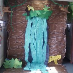 love the idea of a waterfall - cut out leaves and use blue streamers for the water - don't need to do all the rock and such preschool classroom jungle, jungle themed classroom ideas, classroom jungle theme, waterfalls, decorating ideas, bulletin boards, waterfall bulletin board, jungle theme classroom ideas, rainforest
