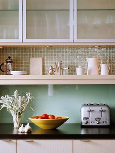 Plate glass and glass mosaic tiles between the shelf and the cabinets as backsplashes