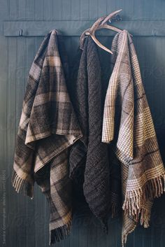 Blankets hanging on coat hooks with antlers by Sandra Cunningham