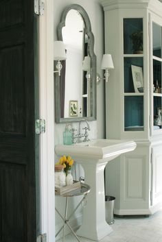 elegant details.  moorish-style mirror, sconces, pedestal sink, turquoise inside the cabinet, and accent table.