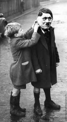 A young boy adjusts his friend's Adolf Hitler mask during a game on a street in King's Cross, London UK, 1938. Photo by William Vanderson/Getty Images.