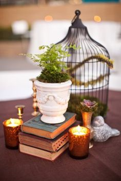 This is kind of the look that I'm going for with old books stacked up to give height, a lantern, some random glass bottles to hold flowers or candles, random little animal, art, or film related pieces, terracotta pots with succulents, and probably crape paper flowers for color.