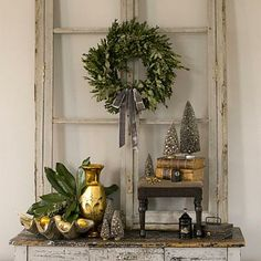 Beyond Red and Green | When displaying a wreath, consider the surrounding items. Here, a silver bow echoes the silver patina of a collection of vintage Christmas trees and mercury glass. | SouthernLiving.com