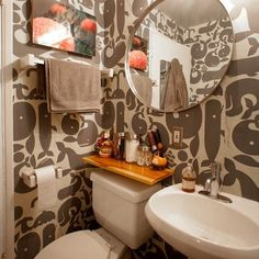 Cool wallpaper in this tiny bathroom. Also, like the floating shelf above the toilet.