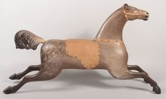 """Sold For $ 1,000  Carved and Painted """"Flying Horse"""" Figure. May have been with a swing as there is no pole hole for carousel. Animal is painted as a gray dapple with yellow glass eyes, buff leather saddle and bridal with faceted upholstery tacks. Unmarked. 28""""h. X 50 1/4""""l. X 8""""w. Condition: Good with use wear.                            Condition report           Condition: Good with use wear."""