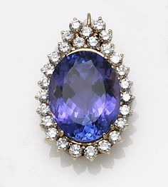 A tanzanite, diamond and fourteen karat gold pendant  the oval-shaped tanzanite within a round brilliant-cut diamond frame; tanzanite weighing approximately: 33.00 carats; estimated total diamond weight: 2.50 carats.