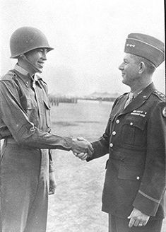 2nd Lt. Ernest L. Childers (Creek), being congratulated by Gen. Jacob L. Devers (on the right) after receiving the Medal of Honor while serving with the U.S. Army's 45th Infantry Division, 180th Infantry Regiment, C Company in Italy during World War II - 1944