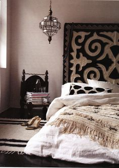 Moroccan rug and wedding blanket, graphically bold black and white headboard, global feel in a neutral bedroom