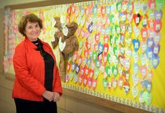 Principal Alana Callahan stands in front of a bulletin board at Park City Magnet School where staff and students have each signed a pledge o...