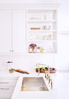 White Chevron tile backsplash and gold fixtures add interest in this light, bright kitchen.