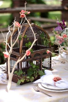 Birdcage-Centerpiece  Branch will have purple fake flowers glued to the branch(s), with the vine going through out the birdcage and entangled in the vines the words saying happily ever after