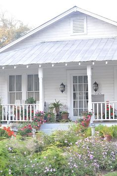 cottage home and a yard full of flowers.