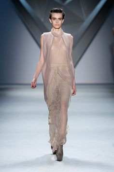Nude melton cutaway high-low vest over nude silk chiffon sleeveless gown with cowl neck and net lace insets with nude techno stretch bermuda short.