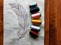 """Maureen Hensel Cracknell has been creating lovely thread sketching with Aurifil  """"This sketch began with a rectangle piece of Art Gallery Fabrics Pure Element in Sweet Mint quilted to a scrap piece of StitchnSew fleece by Therm O Web. Next I pulled from my box set of colorful #Aurifil 50wt and my jar O' Aurifil a thread color story that matches Wild & Free, and I began to freely sketch stitch a simple feather."""""""