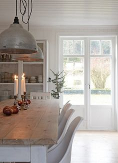 farm table with white chairs. white kitchen.