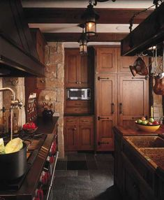 Craftsman/Old World Refrigerator Panels - A potfiller faucet over the range provides modern convenience—as does the side-by-side refrigerator, which is integrated into the cabinetry with custom panels and distinctive wrought-iron hardware. The custom concrete sink looks like a real artifact.