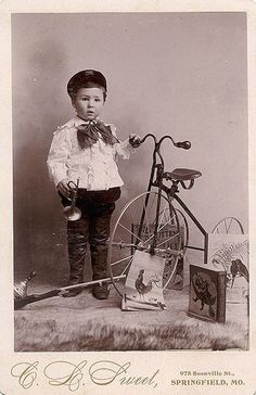 Boy with his tricycle, books, trompet and other toys
