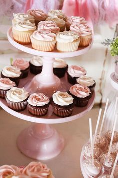 Cupcakes are topped with rose designs in hues of pink and white.