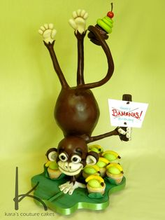 3D Gravity Defying Monkey Birthday Cake - 3D Sculpted Monkey doing a handstand. Coated in ganache then covered and decorated in modeling chocolate. His head and body are cake, as are the cupcakes. Each cupcake is sitting in a sugar paste banana leaf. This cake stood 27 inches tall.