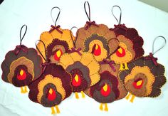 """Felt Turkey Ornaments - These delightful little handmade gobblers were made as a gift for a friend who loves to hunt, but these would be a great addition to anyone's Fall holiday decor.     Designed in the """"Penny Rug"""" stacked style, ornaments measure 6 inches tall (including feet but minus the ribbon length) by 5.25 inches wide and are decoratively stitched with blanket and straight stitches, and adorned with a bow and ribbon hanger."""