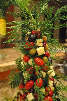 Holiday appetizer tree made of olives, cherry tomatoes and cubes of cheese.