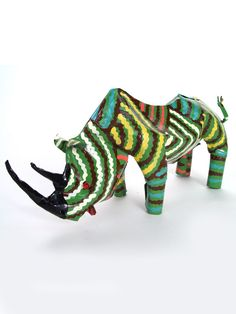 Large Tin Rhino    $36.00. An enormous and strong animal, the rhinoceros symbolizes vigilance and calm. Rhinos are mostly passive creatures, preferring to roam their wide-open grassy spaces in contemplative solitude. They are known for their maternal loyalty, caring and voracious protection of their young. Rhino animal symbolism reminds us to appreciate the expansive bounty we have around us. Made from recycled tin cans in Zimbabwe.