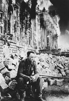 The Battle of Berlin rages on but this German soldier takes a break. Behind him the Reichstag building is in flames. April 1945.