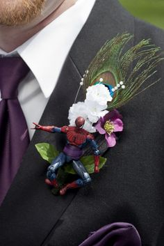 Handmade Action figure Boutonnieres with purple and white flowers and peacock feathers. This groomsman had spiderman.