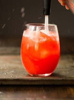 strawberry orange rum punch | 3-4 medium strawberries, hulled 1 1/2 teaspoons organic cane sugar 2 ounces (1/4 cup) blood orange juice (from 1 medium blood orange) 1 ounce (2 tablespoons) meyer lemon juice (or 1/2 ounce regular lemon juice) 1/2 ounce (1 tablespoon) lime juice 1 1/2 ounces (3 tablespoons) white rum 1/2 ounce (1 tablespoon) dark rum ice about 2 ounces sparkling water strawberry and blood orange slices, for garnish