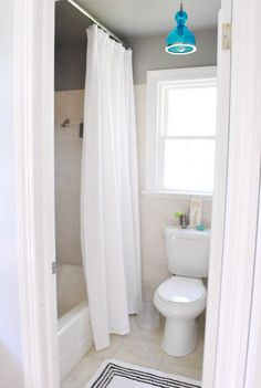 Inexpensive makeover for a tiny bathroom from Young House Love. (Best tip: hang your shower curtain higher to make the room look taller!)