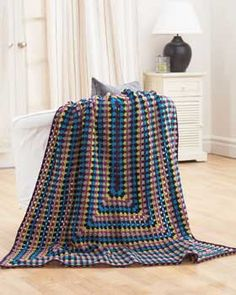 This great, easy blanket is one giant modified granny square. Keep crocheting for an extra-large version. Shown in Bernat Super Value.