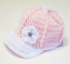 Pretty pink crochet baby baseball cap for a girl in pink with a flower.