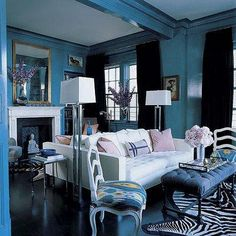 turquoise blue glossy walls paint color, mirrored walls, white tufted modern sofa, polished chrome modern floor lamps, pink pillows, white & black zebra cowhide rug, blue tufted bench and black velvet drapes.
